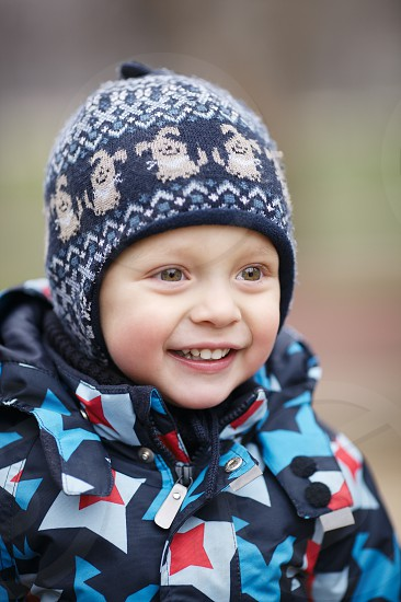 Cute happy little boy with a beautiful beaming smile dressed in a warm jacket and knitted woolly cap photo