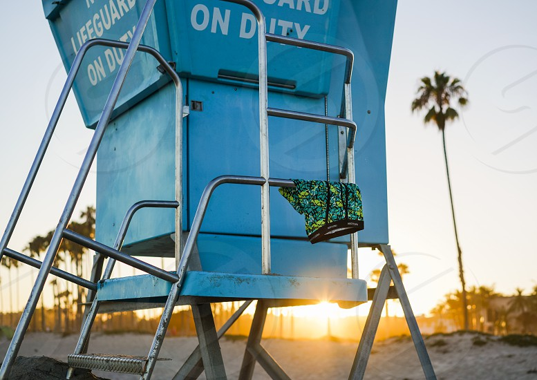 blue green boxer shorts hanging on stainless steel ladder beside blue lifeguard post during sunset photo