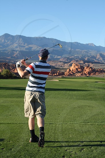 golfer wearing gray cargo shorts completing swing on green grass field photo