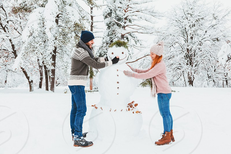 Young couple making snowman in the park photo