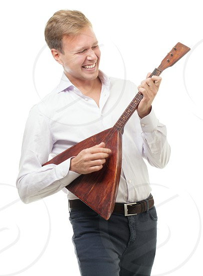 Happy young man playing balalaika national Russian trichord musical instrument. Isolation on white background photo