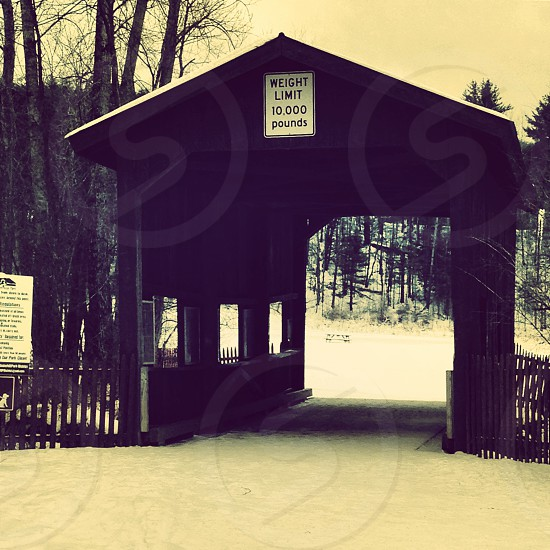 grayscale photography of wooden bridge covered with snow photo