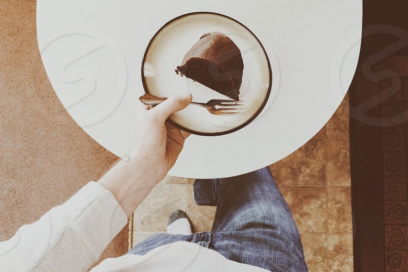 person in blue denim jeans standing in front of sliced of cake photo
