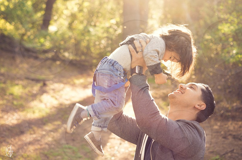 man in grey jacket lifted toddler under sun rays photo