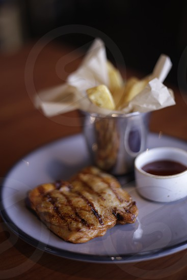Grilled BBQ chicken served on a plate with french fries and tomato ketchup on the table at a restaurant photo
