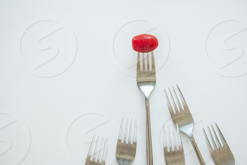 Winner leader. Conceptual shot of fork with cherry tomato leading from other forks. photo