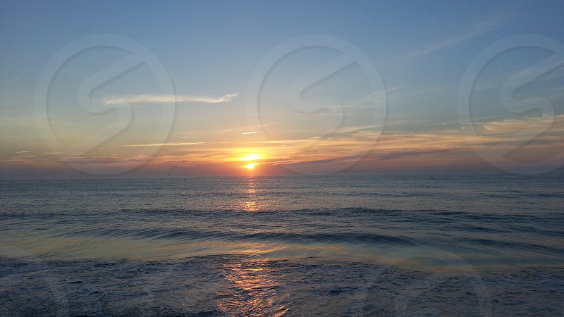Sunrise or sunset over ocean water photo
