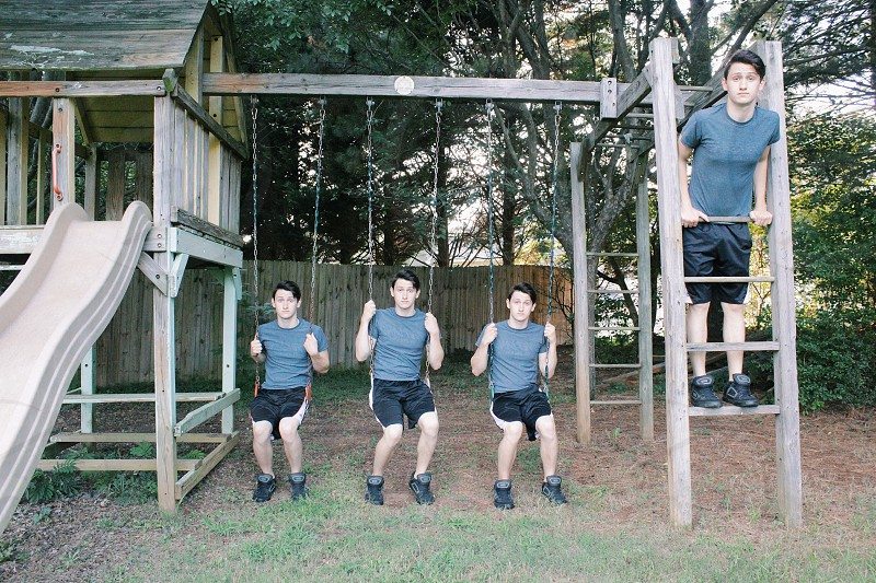 3 men sitting on swing photo