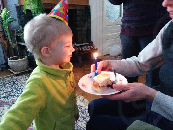 child standing in front of a woman holding a piece of cake with a birthday candle photo