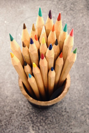 sharpened color pencils sticking out of a wood cup photo