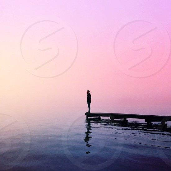 man standing at the end of the dock near water below purple sky during sunset photo