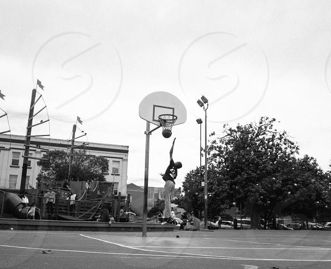 grayscale boy playing basketball photo