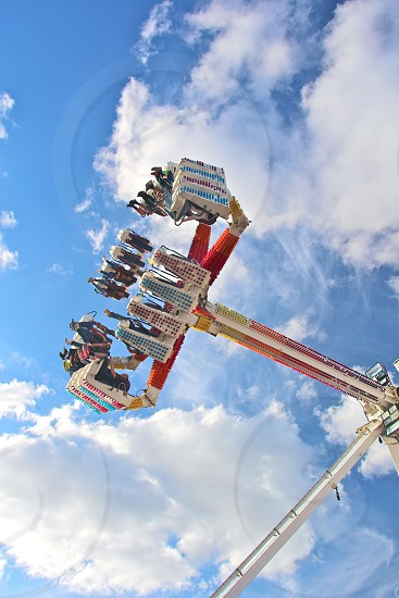 amusement park ride where people sit in seats with legs dangling and the ride spins photo