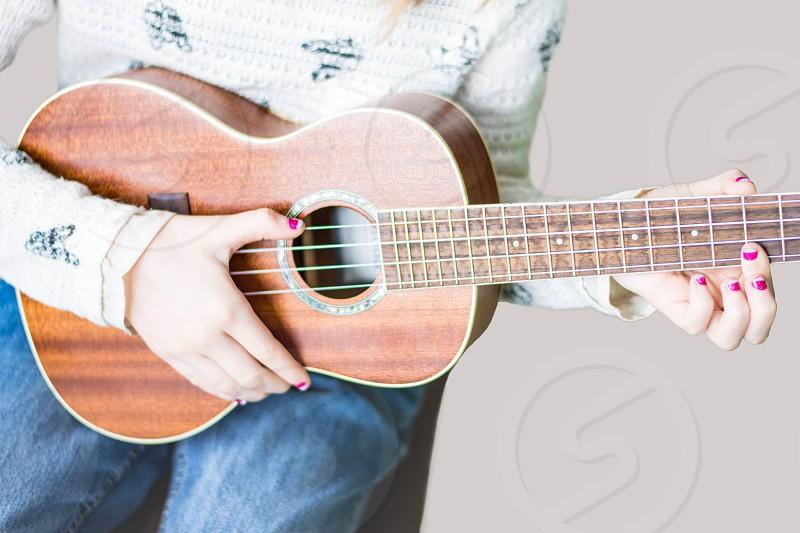 Closeup of child playing ukulele photo