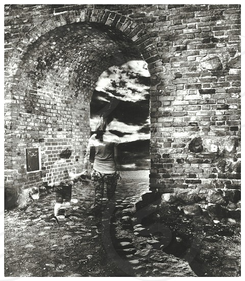 haluccination of 2 person walking towards brick archway in grayscale image photo