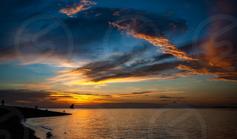 Tropical sunset in Stone Town. Dhow in the horizon and dramatic colorfull cloudy sky. photo