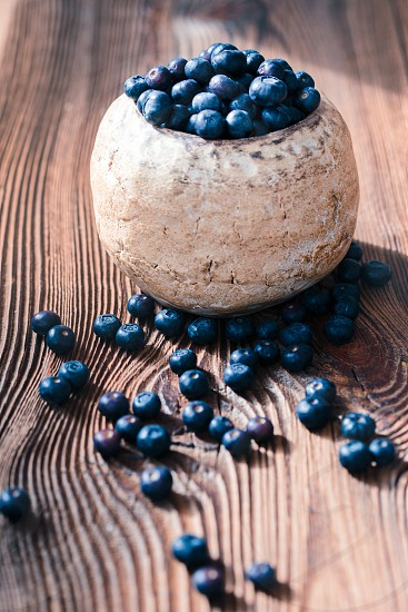 Freshly gathered blueberries put into old ceramic bowl. Some fruits freely scattered on old wooden table photo