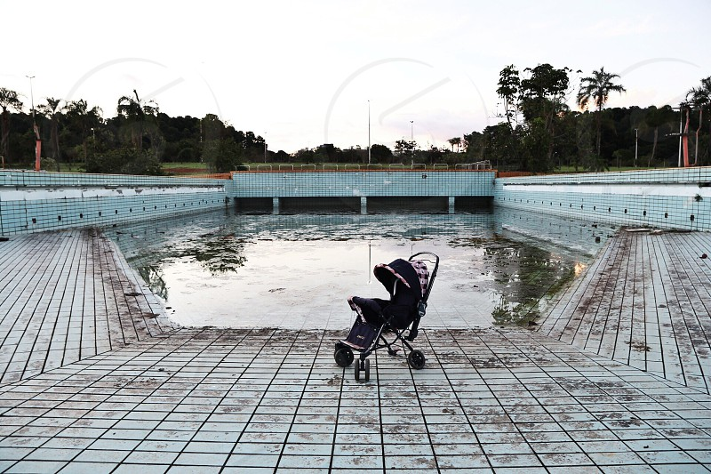 black baby stroller on gray floor tiles photo