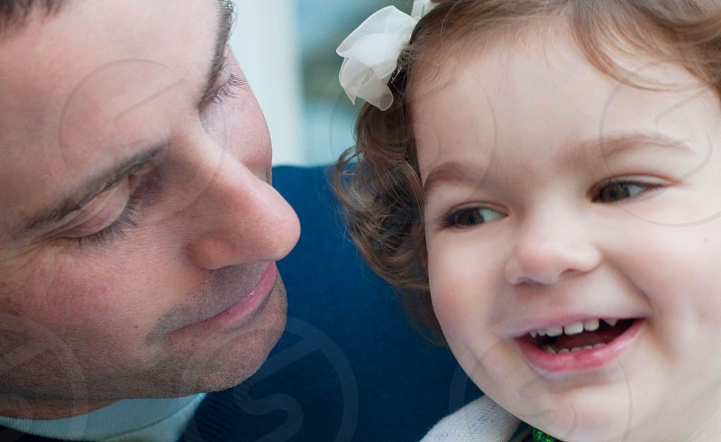 smiling man in blue shirt looking at smiling girl with white ribbon on her hair photo