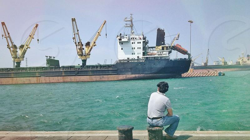 man sitting on bollard looking into ship photo