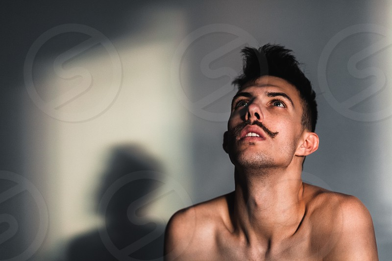 Young shirtless man in despair by the window photo