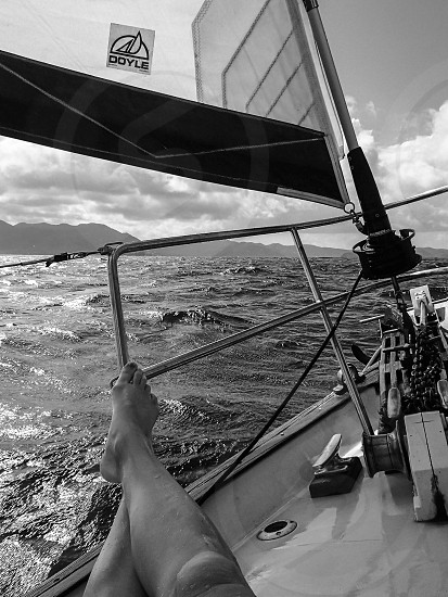grayscale photo of person legs hanging on stainless steel boat rail during daytime photo