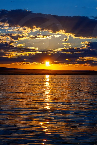 Vertical image of a blue and golden sunset with God rays over the water of Wahweap Bay at Lake Powell Arizona on a summer evening.  Dust rises over a dirt road in the background. photo