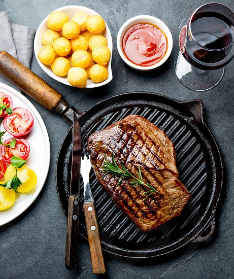 Grilled beef steak on grill pan served with tomato salad potatoes balls and wine. Barbecue bbq meat beef tenderloin. Top view slate background. photo