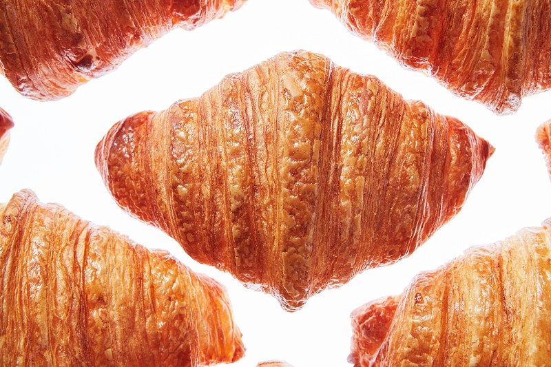 Close up french homemade crispy croissants pattern on a white background. Continental breakfast concept. photo