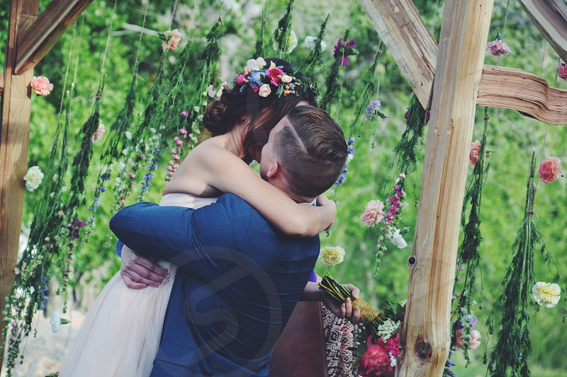 bride and groom kissing under canopy during daytime photo