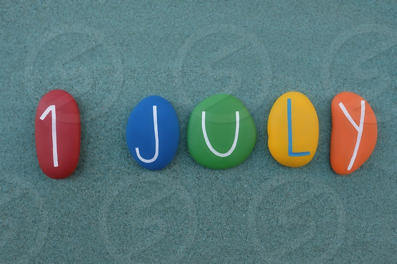 1 July calendar date composed with multi colored stones over green sand photo