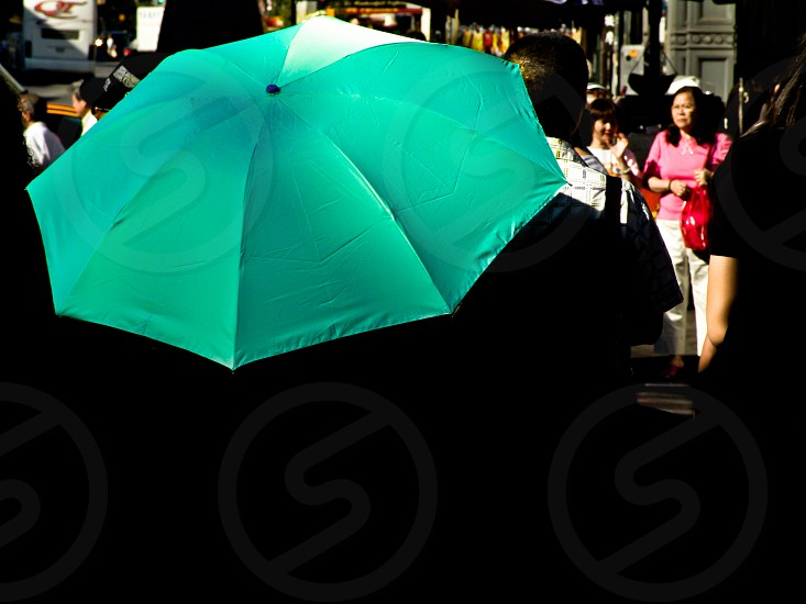 Umbrella surrounded by walking people in the market photo