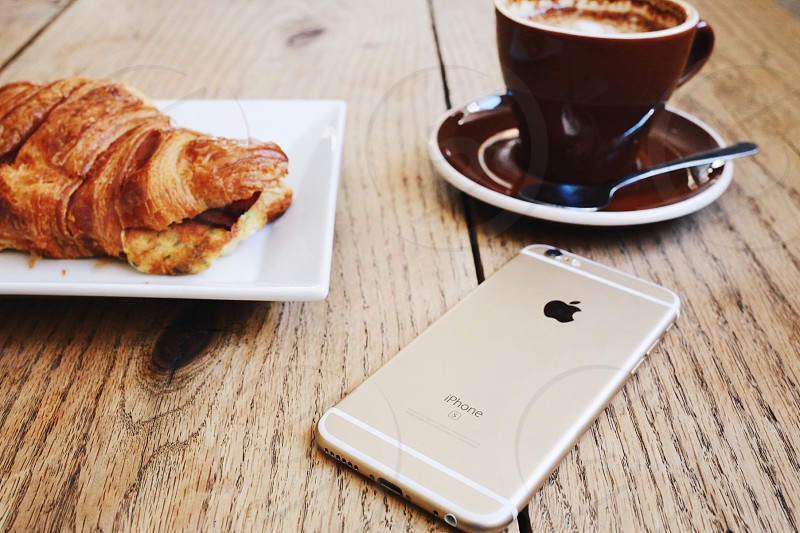 gold iphone 6 near brown ceramic mug on brown ceramic saucer near brown french croissant on white square ceramic plate photo