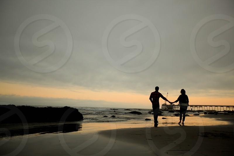 couple beach sunset silhouette ocean photo