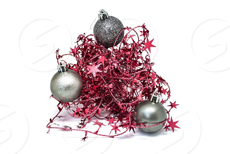 Silver Christmas ball in a red garland with stars on a white background. photo