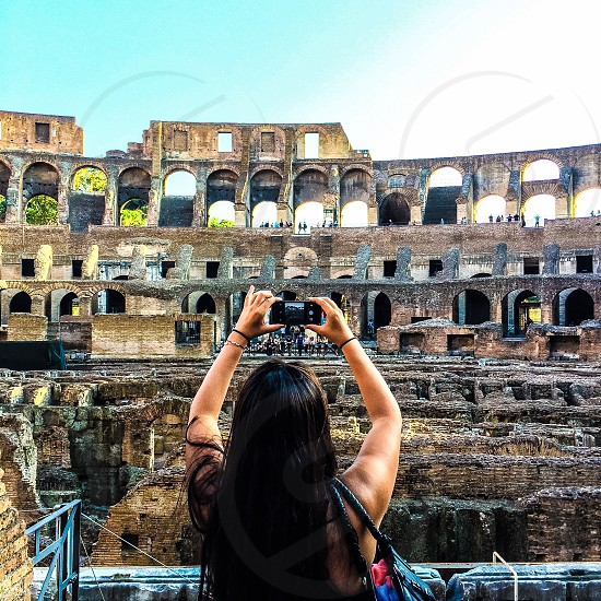 woman taking photograph of Roman coliseum at daytime photo