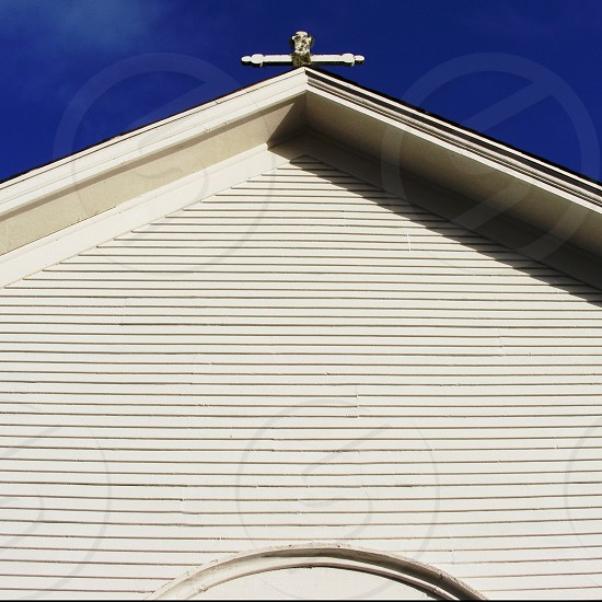 Looking up at the top of a rustic white church with a cross on top photo