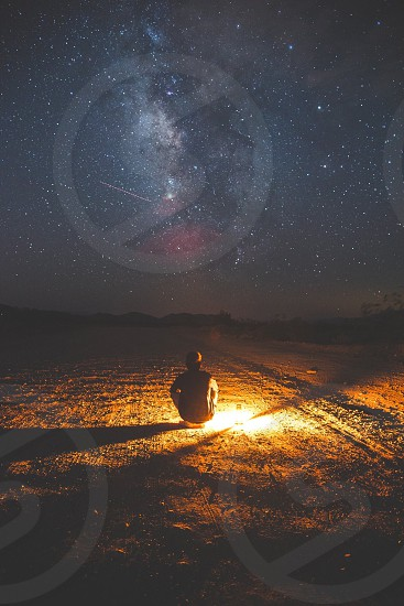 person sitting on brown field beside camping lantern watching the sky photo