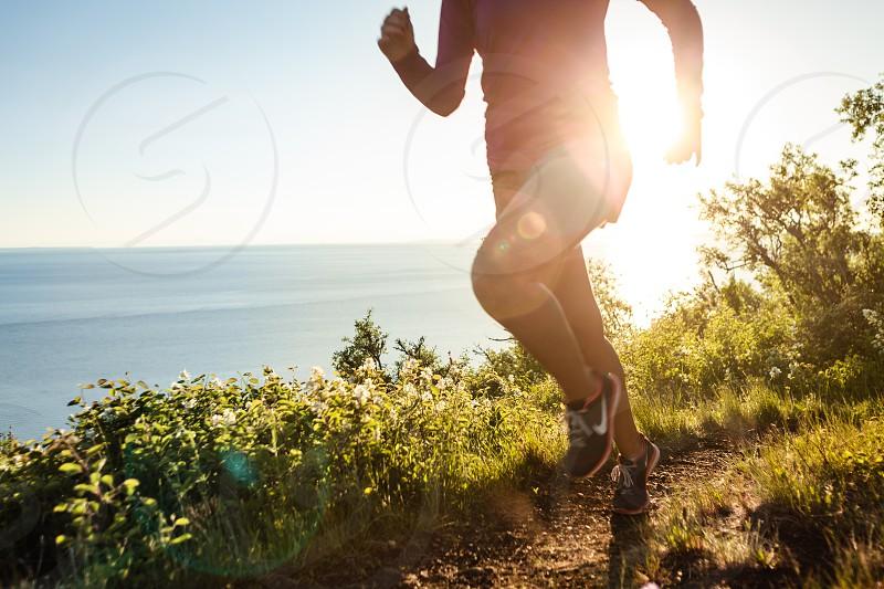 Woman running along trail sunset flare photo