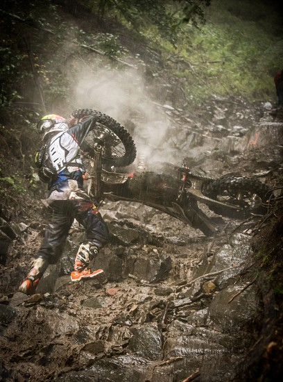 Hard enduro rider trying to stop his bike from falling all over him. photo