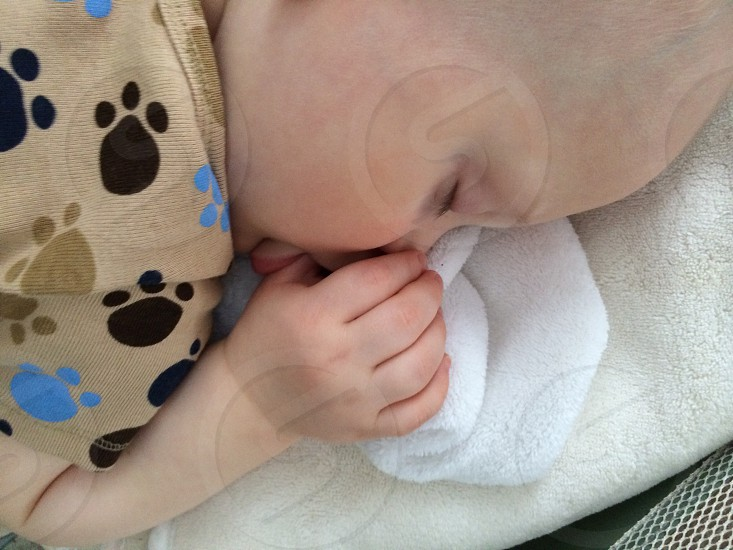 baby lying on white fabric cloth photo