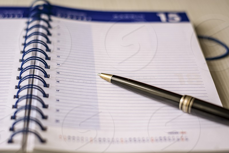 a black pen on an open spiral notebook. Business and scheduling concept photo