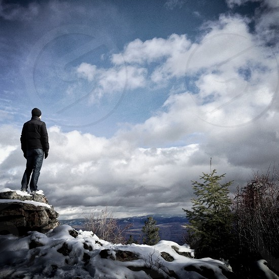 man standing on mountain clip view photo