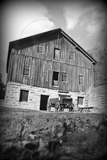 grayscale photography of vehicle parked in front of house during daytime photo