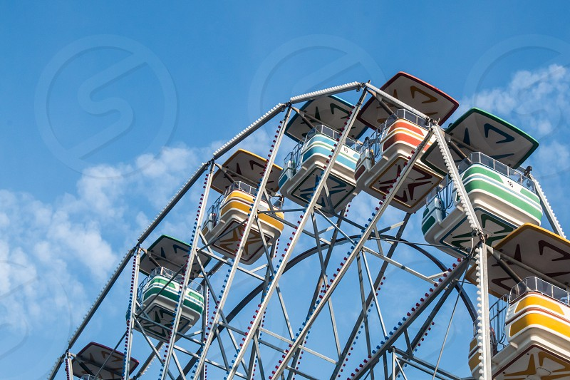 The top half of a ferris wheel with a background of blue sky and clouds. photo