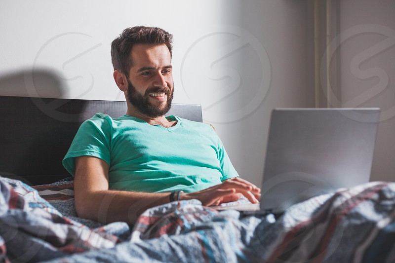 Young man lying in the bed working on a laptop photo