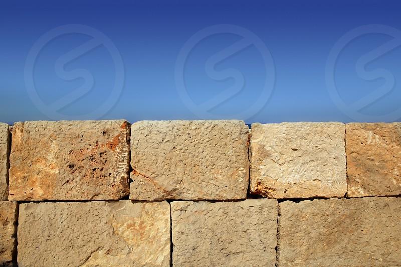 Big stone bricks masonry wall on port dock under blue sky photo