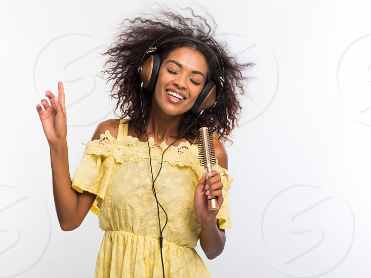 Young pretty african american woman in yellow dress singing and dancing with hair dryer instead microphone at white wall. Black girl having fun isolated on background photo