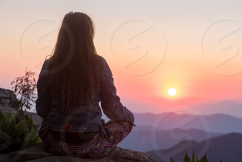 Woman looking at the sunrise up in the mountains while meditating  photo