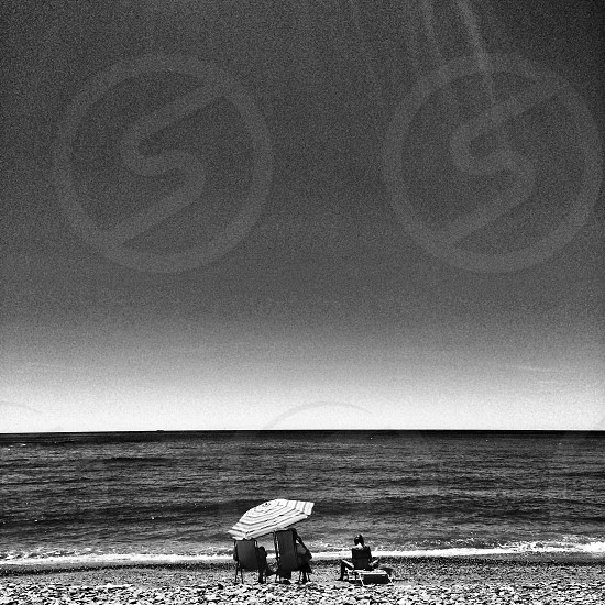 3 people on beach in grayscale photography photo